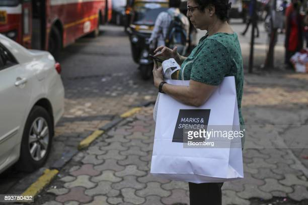 A shopper carrying a Marks Spencer Group Plc branded shopping bag uses a smartphone in Mumbai India on Friday Dec 15 2017 India's inflation surged...