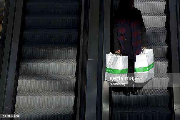 A shopper carrying bags from Laura Ashley Holdings plc stands on an escalator inside the Westfield London shopping mall operated by Westfield Corp in...