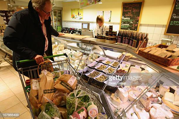 A shopper chooses from organic cheese varieties at a branch of German organic grocery store chain Bio Company on January 10 2011 in Berlin Germany...