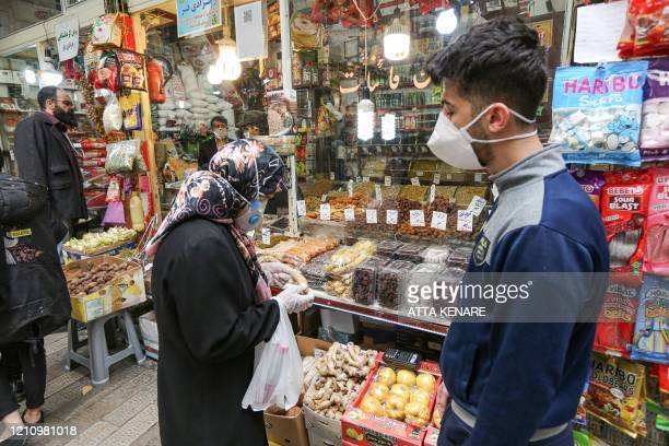 Shopper clad in a face mask and latex gloves, due to the COVID-19 coronavirus pandemic, inspects ginger from at a spice merchant in Tajrish Bazaar in...