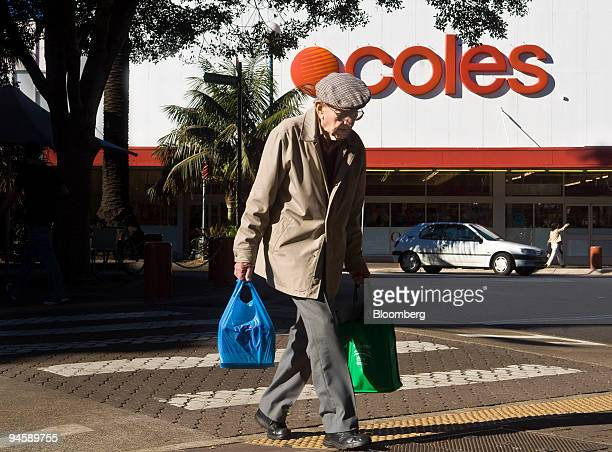 A shopper crosses an intersection outside a Coles Group Ltd supermarket in Sydney Australia on Saturday July 7 2007 Wesfarmers Ltd whose takeover of...