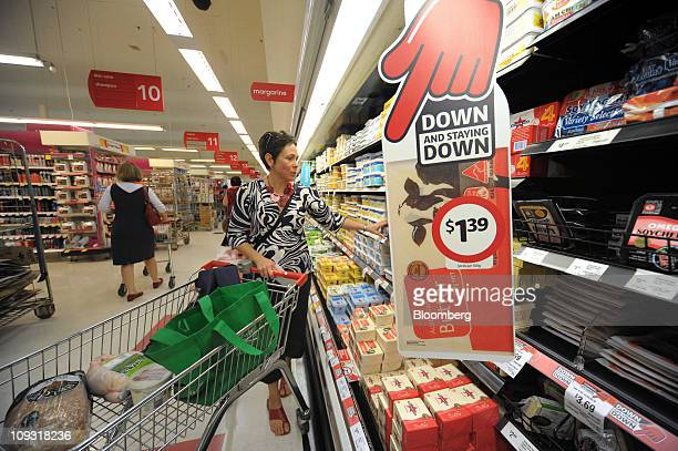 Shopper Dianna Falini selects products from the dairy section behind a sign advertising lowered prices of butter at a Coles Group Ltd supermarket in...