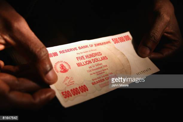 A shopper displays a five hundred million dollar Zimbabwaen bank note June 29 2008 in Bulawayo Zimbabwe With the economy in free fall and with the...