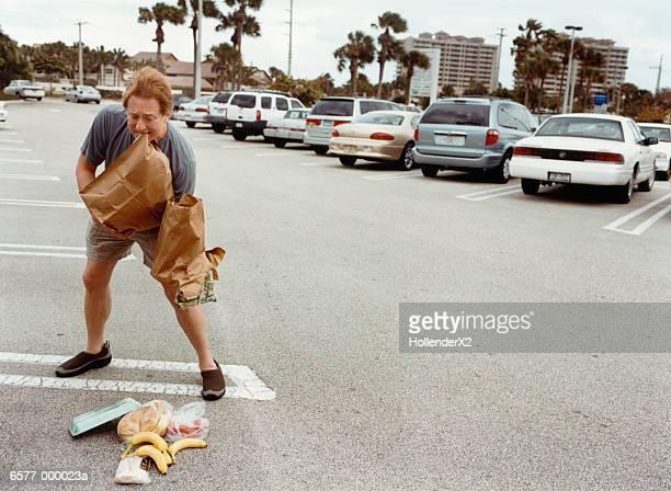 shopper dropping groceries - clumsy stockfoto's en -beelden