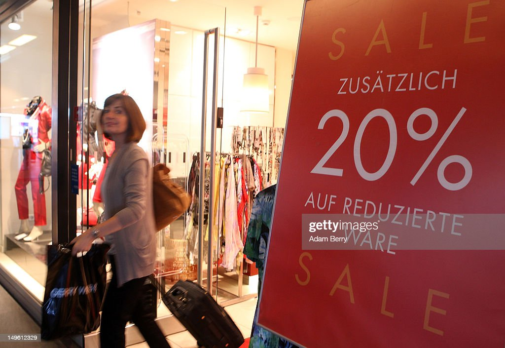 A shopper exits a store advertising summer sales on August 1, 2012 in Berlin, Germany. German retailers began their annual summer clearance sale on Monday, offering deep discounts of up to 80 percent on warm weather items as they prepare to stock up for the autumn shopping season.