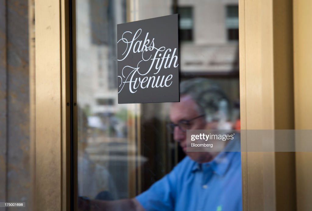 A shopper exits Saks Fifth Avenue in New York, U.S., on Monday, July 29, 2013. Hudson's Bay Co. agreed to buy Saks Inc. for $2.4 billion, combining Canada's largest-department store chain with one of the most prestigious U.S. luxury retailers in a deal that may spur the creation of a real estate investment trust. Photographer: Scott Eells/Bloomberg via Getty Images