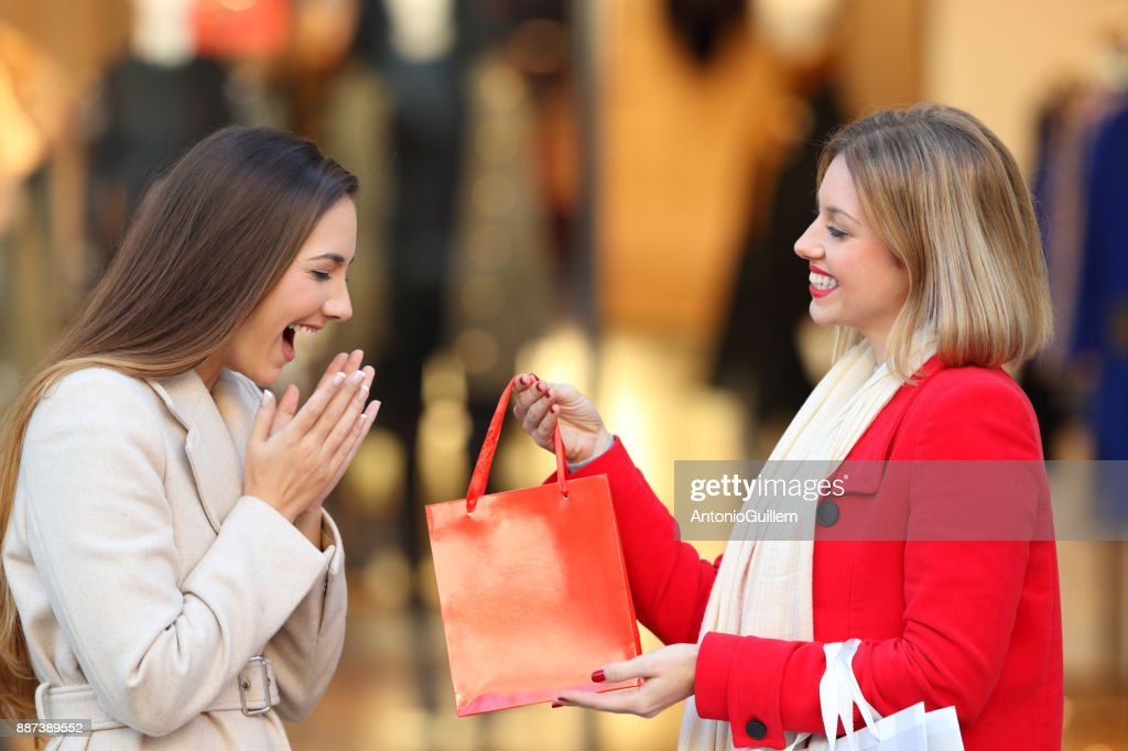 Shopper giving a gift to a friend in winter : Stock Photo