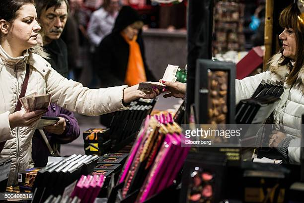 A shopper hands over 500 Hungarian forint banknotes to a market trader at the Christmas market in Vorosmarty square in Budapest Hungary on Saturday...