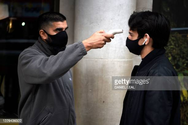 Shopper has his temperature taken at the entrance to the Apple store in Regent Street, central London on November 3 as the country prepares for a...