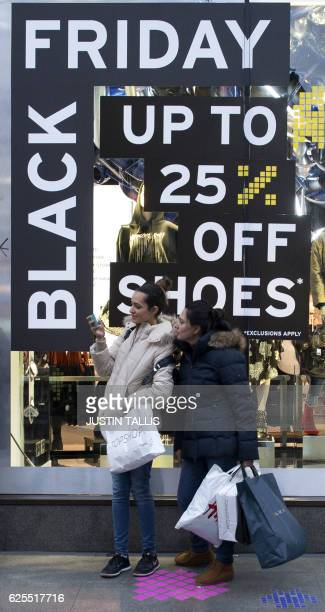 Shopper hold bags as they stand alongside a retail store's 'Black Friday' advertisement on Oxford Street in central London on November 24 ahead of...
