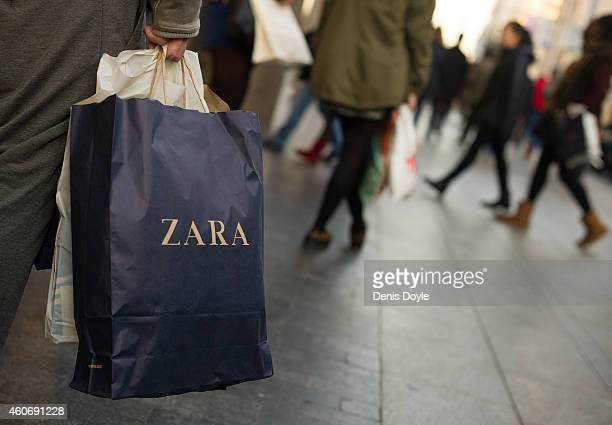 A shopper holds a a branded paper shopping bag from the Zara fashion store operated by Inditex SA on Gran via street on December 19 2014 in Madrid...