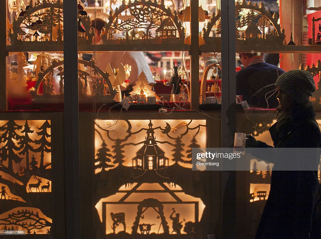 A shopper holds a beverage as she walks past a decorated stall at a market ahead of Christmas in Berlin, Germany, on Sunday, Dec. 1, 2013. Euro-area economic growth slowed to 0.1 percent in the third quarter after a 0.3 percent gain in the previous three months. Photographer: Krisztian Bocsi/Bloomberg via Getty Images
