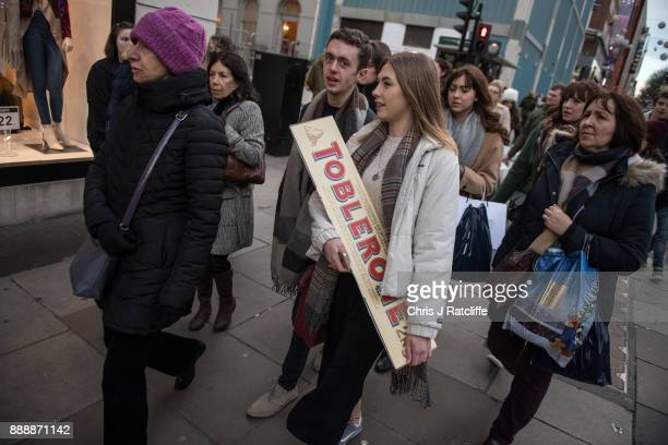 A shopper holds a giant Toblerone chocolate bar on Oxford Street on December 9 2017 in London England With two weeks of shopping time left before...