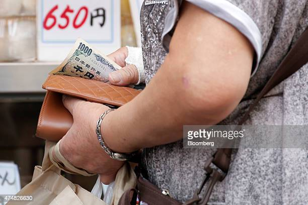 A shopper holds a Japanese 1000 yen banknote at a store in the Sugamo district of Tokyo Japan on Sunday May 24 2015 Japan's Topix index fell for the...