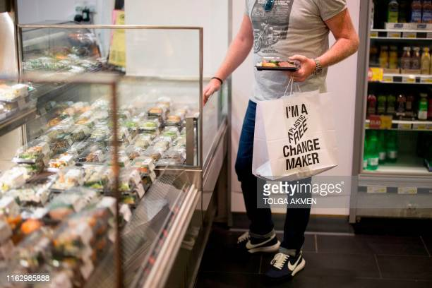 Shopper holds a paper bag with a slogan promoting plastic-free packaging shops at Budgens supermarket in Belsize Park, north London on July 2, 2019....