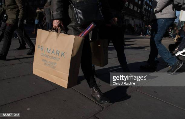 A shopper holds a Primark shopping bag on Oxford Street on December 9 2017 in London England With two weeks of shopping time left before Christmas...