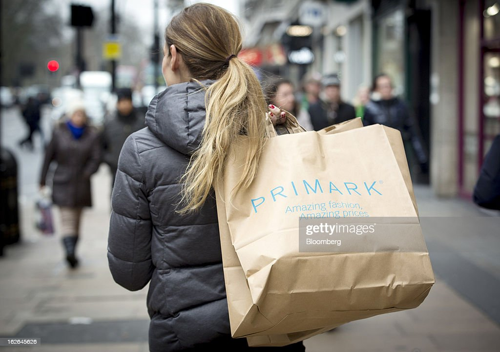 A shopper holds a Primark shopping bags while waiting for a bus along Oxford Street, the store is operated by Associated British Foods Plc in central London, U.K., on Monday, Feb. 25, 2013. U.K. Chancellor of the Exchequer George Osborne won't bow to opposition calls to change economic plans after the decision by Moody's Investors Service to strip the U.K. of its Aaa status. Photographer: Jason Alden/Bloomberg via Getty Images