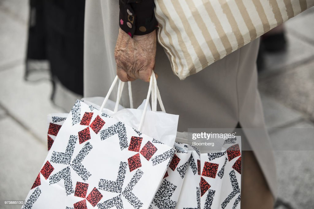 A shopper holds bags as she walks in the Ginza district of Tokyo, Japan, on Friday, May 25, 2018. The savings-rich elderly spend about 9.7 trillion yen ($87 billion) a year on their offspring and such spending last year accounted for about a third of the modest growth in total consumption, according to Hiromichi Shirakawa, chief Japan economist at Credit Suisse Group. Photographer: Shiho Fukada/Bloomberg via Getty Images