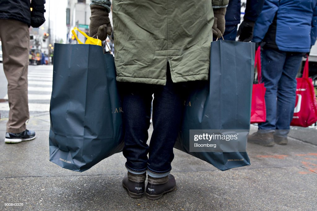 A shopper holds bags from a Zara fashion store, operated by Industria de Diseno Textil SA, while walking through the Magnificent Mile commercial district in Chicago, Illinois, U.S., on Friday, Dec. 29, 2017. Bloomberg is scheduled to release consumer comfort figures on January 4. Photographer: Daniel Acker/Bloomberg via Getty Images