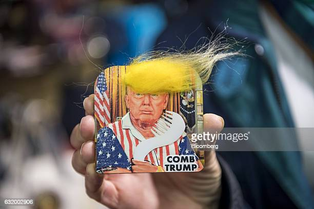 A shopper holds out a US President Elect Donald Trump presidential inauguration memorabilia button for a photograph in the White House gift store in...