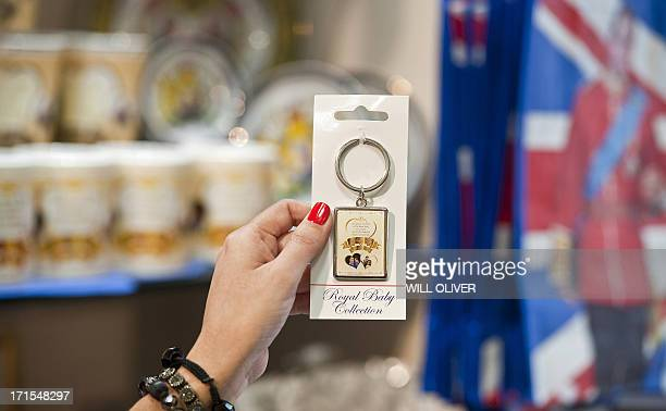 A shopper holds up a keyring one of many souvenir gifts celebrating the upcoming birth of the royal baby of Prince William Duke of Cambridge and...