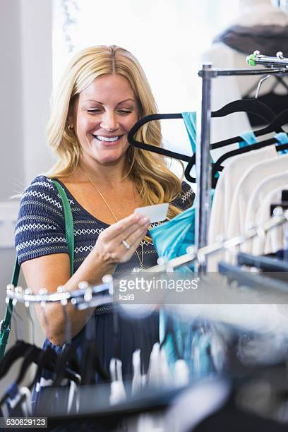 Shopper in clothing store looking at price tag