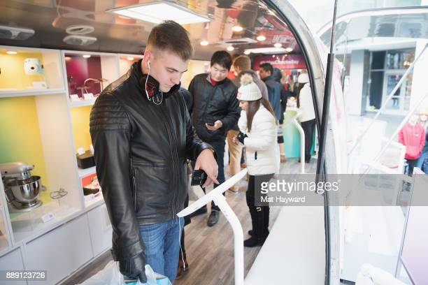 A shopper interacts with the eBay mobile app during the 'Did You Check eBay' Holiday Airstream tour at Westlake Center Plaza on December 9 2017 in...