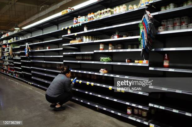 Shopper is seen in the pasta aisle of a supermarket in Bethesda, Maryland on March 16, 2020. - Stocks tumbled on March 16, 2020 despite emergency...