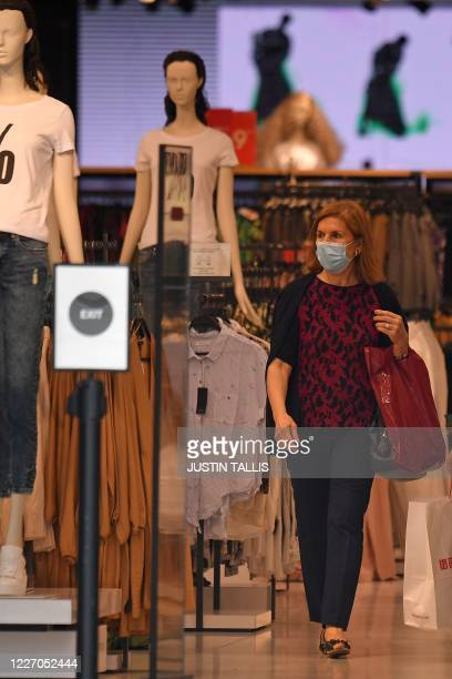 A shopper is seen wearing a mask as a precaution against the transmission of the novel coronavirus as she shops in Reserved on Oxford Street in...