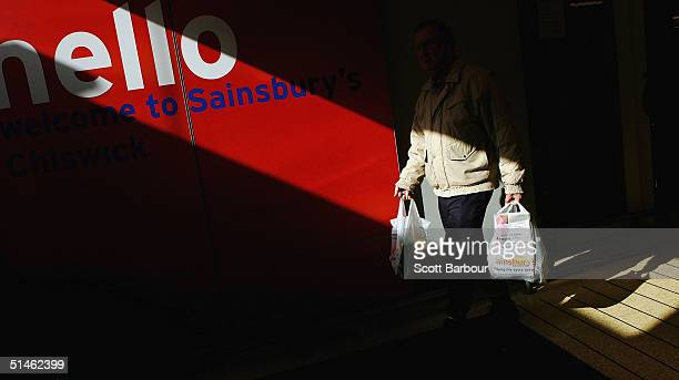 A shopper leaves a Sainsbury's supermarket carrying shopping bags on October 11 2004 in London England Sainsbury's Britain's thirdlargest food...