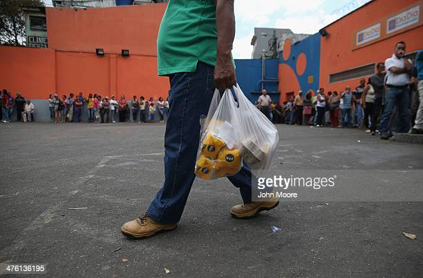 A shopper leaves a supermarket with flour and eggs after waiting for hours for scarce foodstuffs on March 2 2014 in Caracas Venezuela Venezuela has...