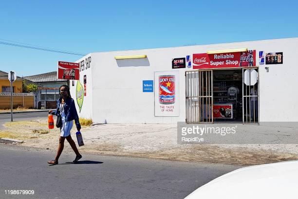 shopper leaving tiny cape town convenience store carrying purchases - província do cabo ocidental imagens e fotografias de stock