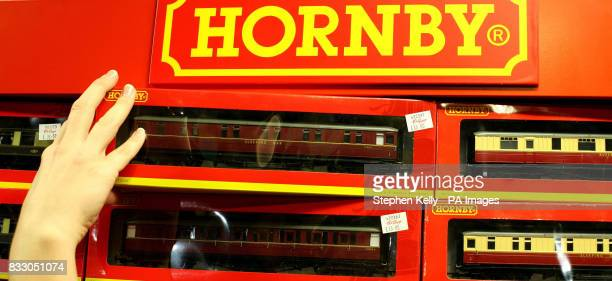A shopper lifts a Hornby train set off the shelf in a toy shop in central London