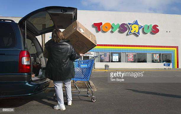 A shopper loads a purchase into her van outside a Toys R Us store January 28 2002 in Arlington Heights IL Toys R Us Inc plans to cut 1900 jobs and to...