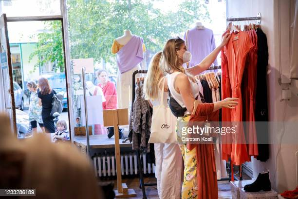 Shopper looking among clothes in a store on the second day that people are no longer required to show a negative Covid test result to enter...