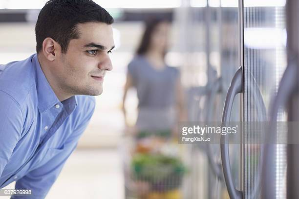 Shopper looking into freezer at supermarket