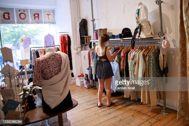 Shopper looks among clothes in a store on the second day that people are no longer required to show a negative Covid test result to enter...