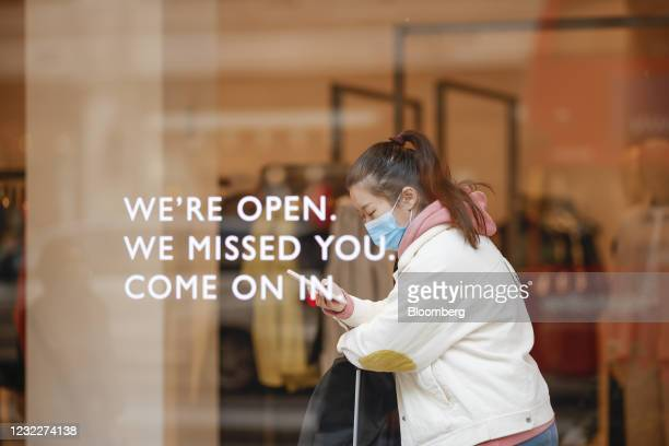 Shopper looks at a smart phone inside a COS store in London, U.K., on Monday, April 12, 2021. Consumers flocked to shopping streets across England on...