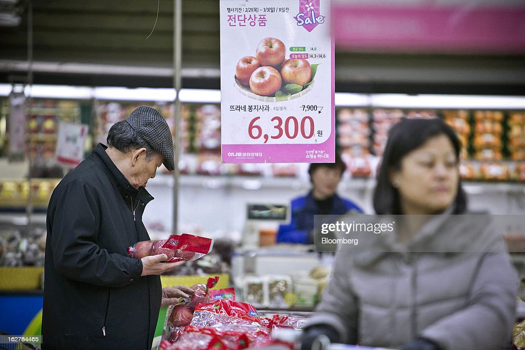 A shopper looks at bags of apples at Hanaro Mart in Seoul, South Korea, on Tuesday, Feb. 26, 2013. South Korean consumer confidence remained at its highest level since May as gains in the won drove down the prices of imported goods. Photographer: Jean Chung/Bloomberg via Getty Images