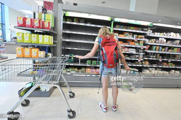 Shopper looks at empty shelves where chilled foods would normally be stocked, inside a Waitrose supermarket in London on September 7, 2021. - Sparse...