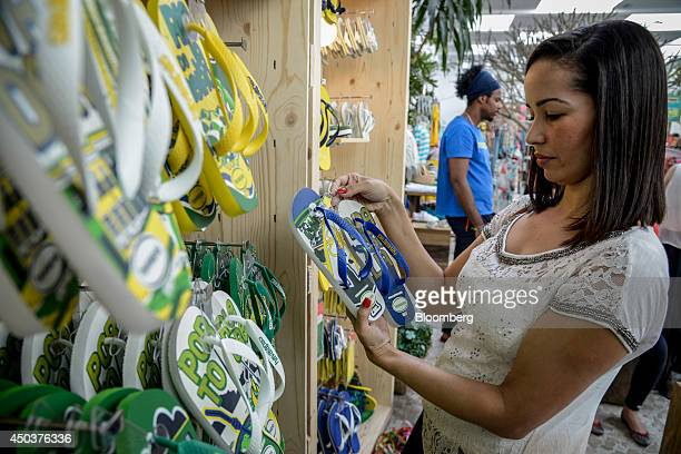 A shopper looks at flip flops at an Alpargatas SA Havaianas store in Sao Paulo Brazil on Saturday June 7 2014 Sao Paulobased Alpargatas SA the maker...