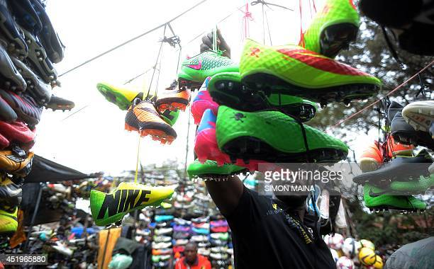 A shopper looks at football shoes displayed in Gikomba Market East Africa's biggest secondhand clothing market on July 10 2014 in Nairobi Locally...