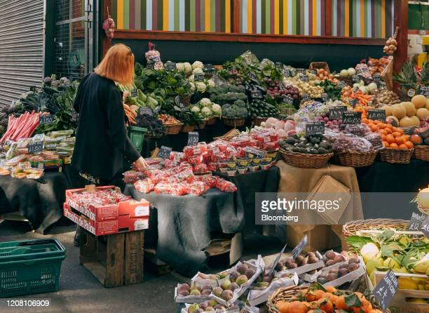 Shopper looks at fresh fruit and vegetables for sale at Borough Market, which has extended its delivery service to support the local community and...