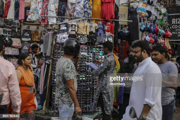 A shopper looks at sunglasses at a roadside stall in Mumbai India on Friday Dec 15 2017 India's inflation surged past the central bank's target...
