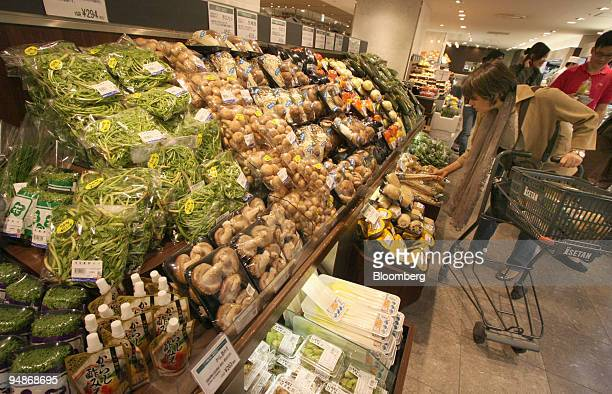 A shopper looks at vegetables in an Isetan department store in Tokyo Japan on Tuesday April 1 2008 Japan's household spending slumped job vacancies...