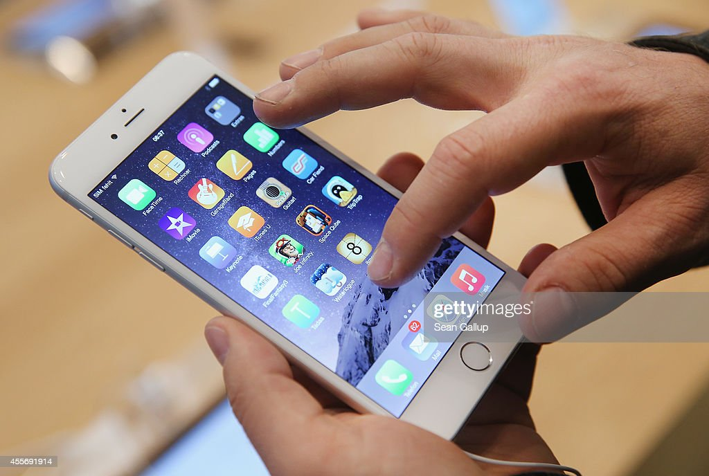 A shopper ltries out the new Apple iPhone 6 at the Apple Store on the first day of sales of the new phone in Germany on September 19, 2014 in Berlin, Germany. Hundreds of people had waited in a line that went around the block through the night in order to be among the first people to buy the new smartphone, which comes in two versions: the Apple iPhone 6 and the somewhat larger Apple iPhone 6 Plus.