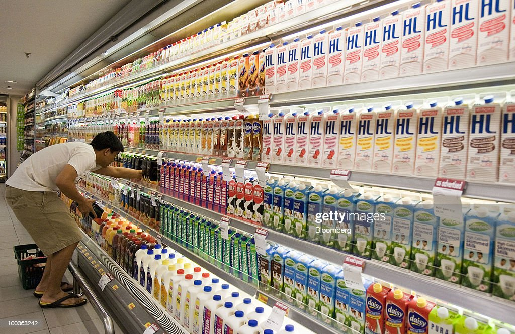 A shopper makes a selection in the refrigerated section of a supermarket in Singapore, on Monday, May 24, 2010. Singapore's consumer prices rose at the fastest pace in 14 months in April as an accelerating economy and a booming labor market boosted housing and transportation costs. Photographer: Charles Pertwee/Bloomberg via Getty Images