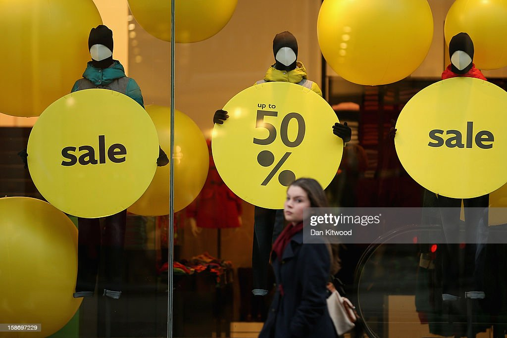 A shopper makes her way past sale signs in the window of a clothing store on Regent Street on December 24, 2012 in London, England. Many high street retailers have started their sales two days early this year on what is expected to be the busiest shooping day of the year.