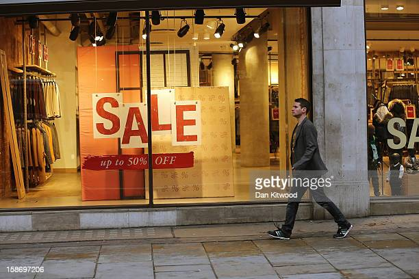 A shopper makes his way past sale signs in the window of a clothing store on Regent Street on December 24 2012 in London England Many high street...