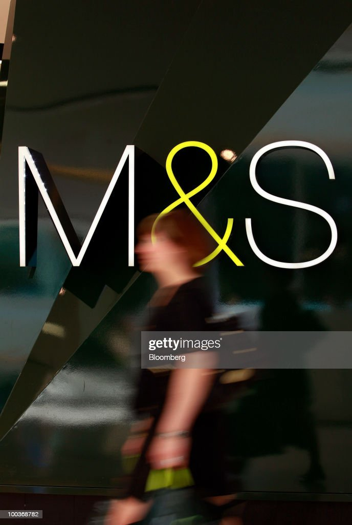 A shopper passes a logo at a Marks & Spencer Group Plc (M&S) store in The Westfield Centre shopping mall in London, U.K., on Monday, May 24, 2010. The company, the U.K.'s biggest clothing retailer, reports its full-year earnings tomorrow. Photographer: Jason Alden/Bloomberg via Getty Images